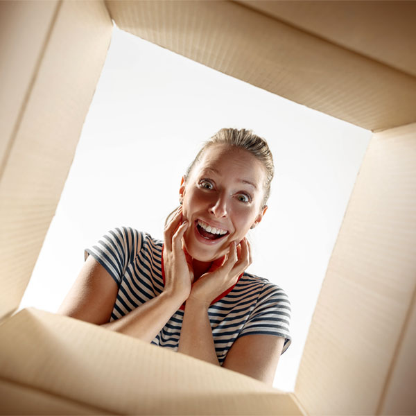 A surprised young lady looking inside a cardboard box